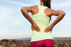 stock-photo-trail-running-runner-with-painful-lower-back-pain-injury-or-strained-muscle-near-the-spine-female-448294519